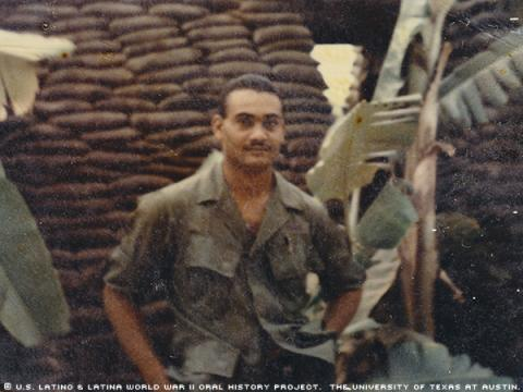 "Germán Abadia-Olmeda E-4 (Specialist 4). This photo was taken in Vietnam in 1969. German was standing in front of a bunker.\Bunkers used to protect ourselves from any attack; were made of wood and sandbags; at my side some banana trees.""-German"""